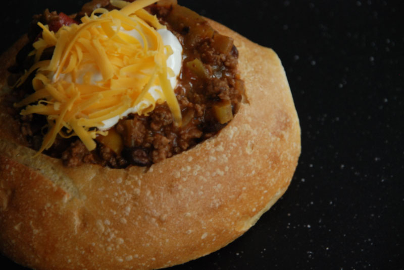 Rainy Day Chili with sour cream and sharp cheddar cheese in a sourdough bread bowl